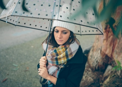 Portrait of young beautiful girl under a umbrella in an autumn rainy day